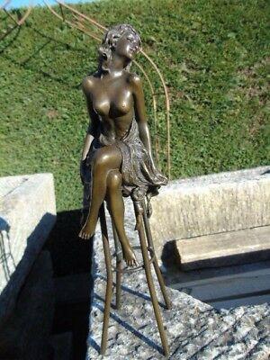 statue d une femme au seins nue sur tabouret en bronze signé .