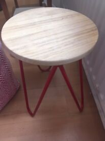 Three-legged hairpin stool with red metal legs and brushed wooden seat