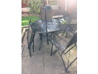 Black glass patio table with four chairs and parasol