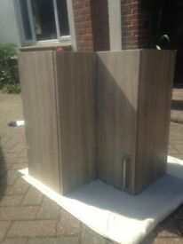 Two grey oak colour rigid wall kitchen units with shelves, fixings and handles