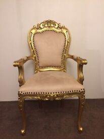 Occasional gold throne chair carved from wood. Cream fabric.