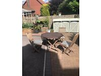used teak outside dining table and four chairs with cushions