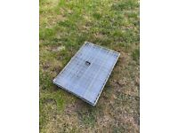 Galvanised steel dog cage with two lockable doors.