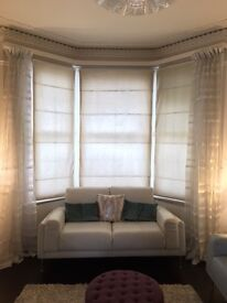Natural Roman Blinds with sidewinder mechanisms and Shimmer Voile Curtains for Victorian Bay Windows