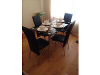 Glass dining table and black chairs