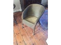 A lovely Lloyd Loom style arm chair, gold paint finish with cushion
