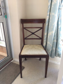Mahogany chair with stylish detail on back and has cream upholstery