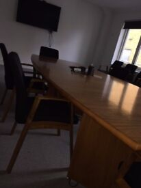 Boardroom style wooden table accompanied by 8 black padded wooden chairs