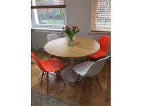 Modern oak veneer round dining table and four Eames inspired chairs