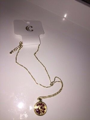 Gold necklace from the store charming charlie circle with small red beads inside