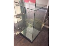 Tall glazed shop display cabinet with internal lights.