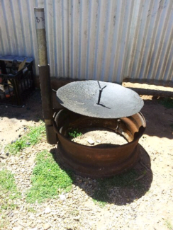 Truck rim fire pit with plow disc hot plate and camp oven hook