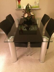 5x3 glass dinning table and black chairs