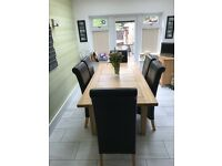 Large real wood oak extendable dining table with 6 faux leather chairs. Free delivery within 2 miles