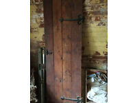 Old wooden door with decorative hinges and latch