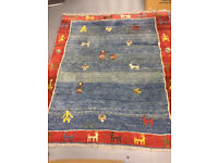 Afghan Rug - primarily blue and red with motifs and fringe
