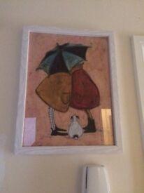 Couple cuddling under an umbrella print in frame