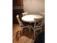 White wooden dining room table and four chairs