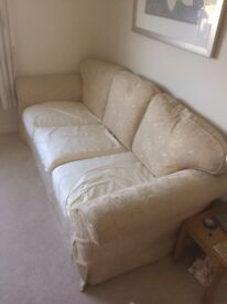 2 x cream sofas with spare set of blue covers