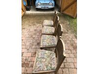 Four Oak dining chairs with fabric seating cushions