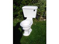 Close flush toilet and cistern. White.