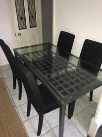 Glass dining table and 4 black chairs