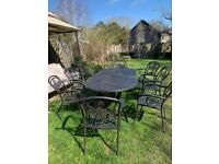 8 seater cast iron garden table and matching chairs