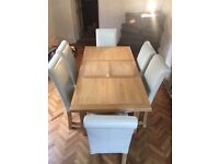 Solid oak extending dining table and six leather chairs