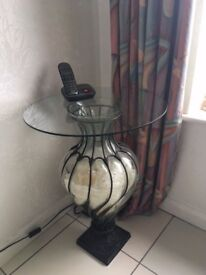 Glass topped table on glass vase stand