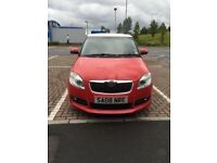 Skoda Fabia red with white roof.