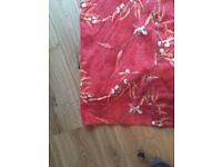 Pair of patterned terracotta curtains pleated with hooks ready for hanging