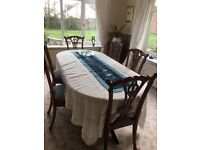 mahogany dining table and six ornately carved chairs