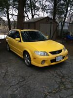 2002 Mazda Protege Sedan. Yellow with dark grey interior