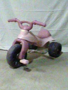 Child pink plastic tricycle