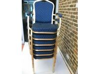 6 stackable armchairs . Gold painted metal frame and blue cover fabric .
