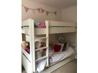 White wooden bunk bed with mattresses and drawer storage