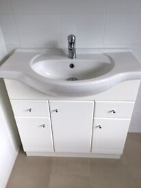 White bow fronted bathroom sink with white multidoor pedestal cabinet.
