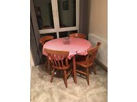 Wooden extending circular dining table and four chairs