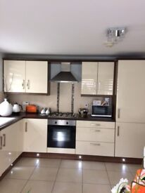 This L-Shaped modern apartment kitchen in High Gloss Cream is in excellent condition