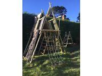 Wooden climbing frame with wobble bridge, climbing wall and scramble net