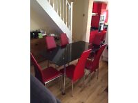 5ft black glass dining table with 6 red faux leather chairs