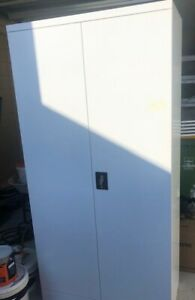 White tall 2 door metal cabinet with keys