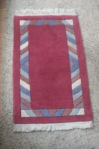 Red rug with border of flowers