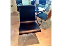 FOUR BLACK LEATHER AND WOOD SWIVEL CHAIRS ON CHROME LEGS