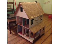 Large traditional wooden dollshouse on castors, vaguely Edwardian-style villa