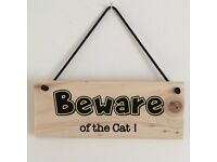 Handmade 'Beware of the cat' sign with rustic feel.