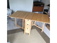 Drop-leaf dining table with 4 chairs. Space-saving solid wood table, seats 6 with storage drawers