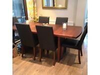large fixed pedestal dining table in oak veneer and 6 side chairs in brown leather