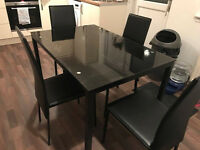 Black glass covered table with 4 matching chairs