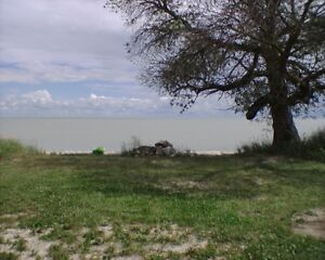 Lakefront, sandy shore lot with trailer, electricity and tank